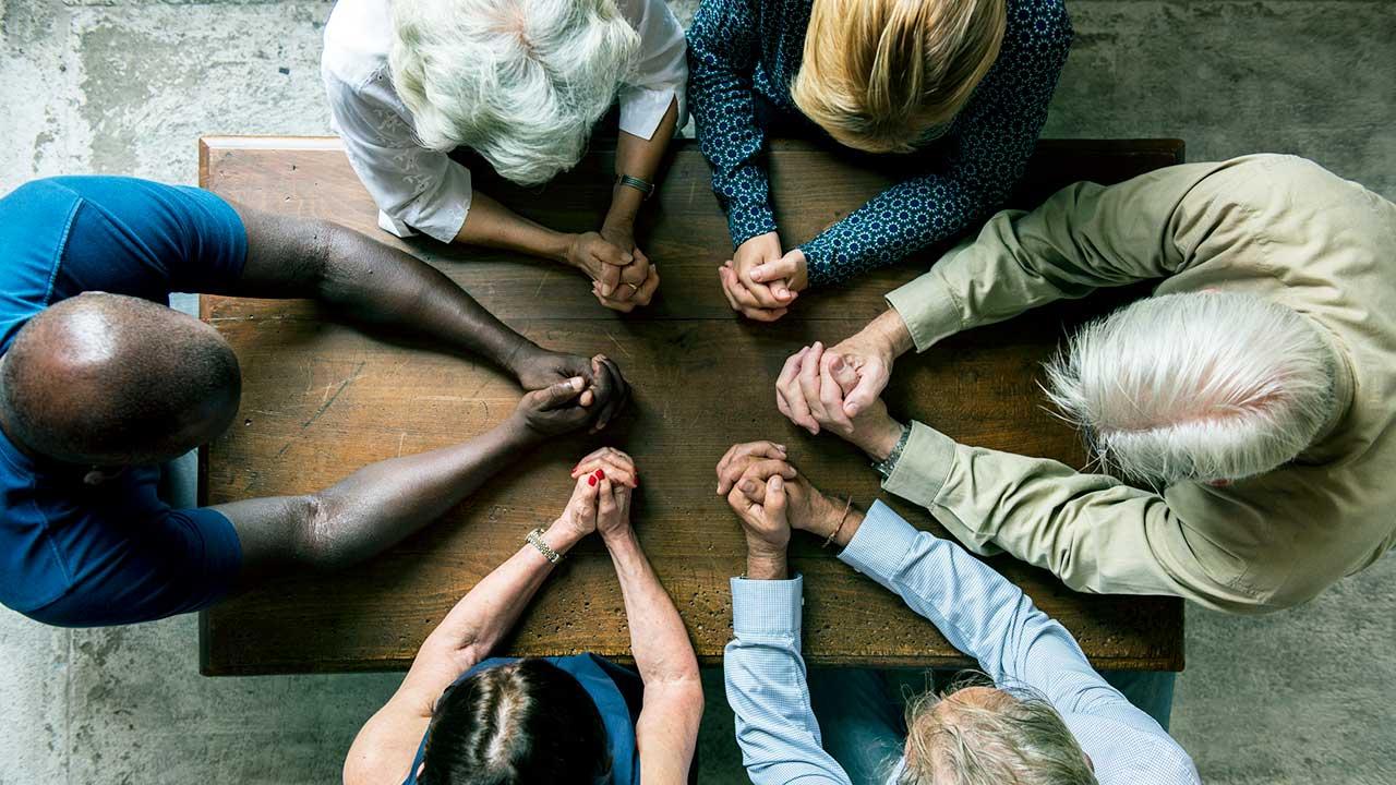 Menschen beten zusammen an einem Tisch