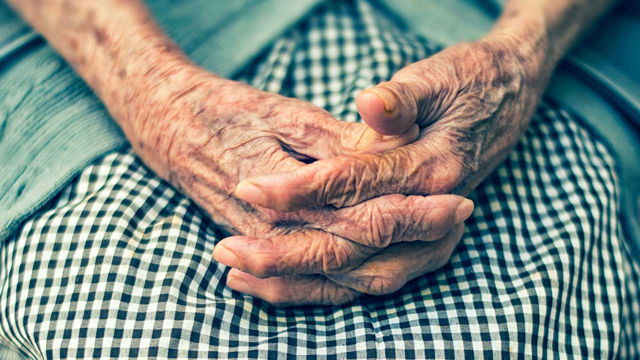 Gefaltete Hände einer älteren Frau