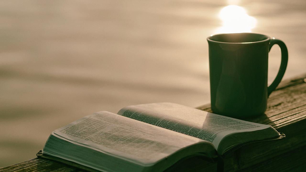 EIne aufgeschlagene Bibel und daneben eine Tasse.