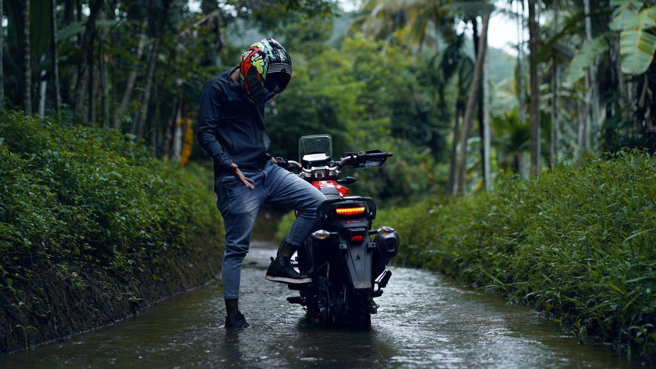 Ein Mann steckt mit seinem Motorrad im Wasser fest.