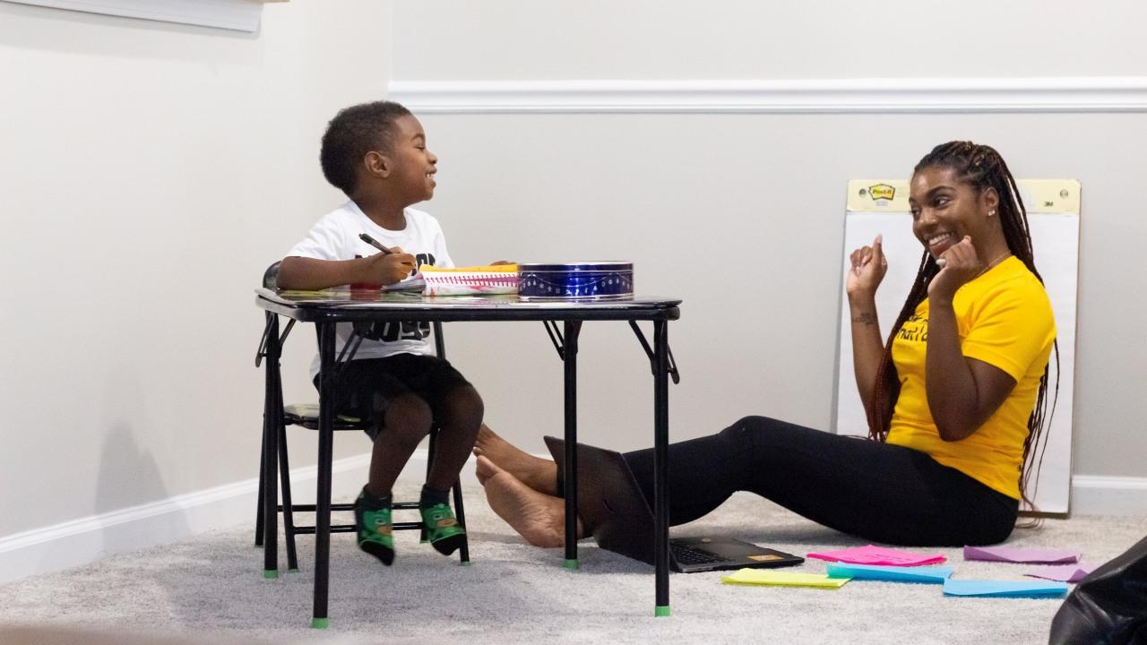 Ein Kind schreibt an einem Tisch, seine Mutter sitzt daneben auf dem Boden. Sie lachen einander an.