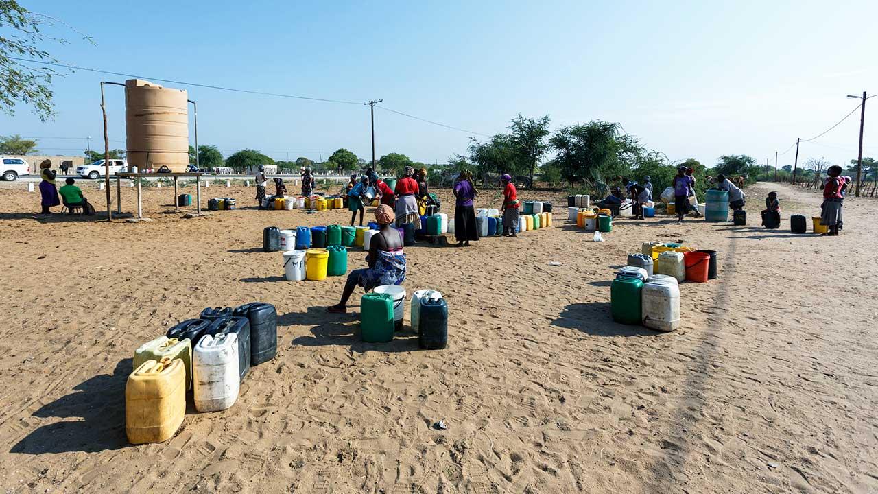 Menschen mit Behältern vor einem Wassertank in Namibia
