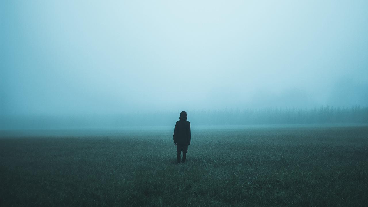 Eine Person steht im Nebel.