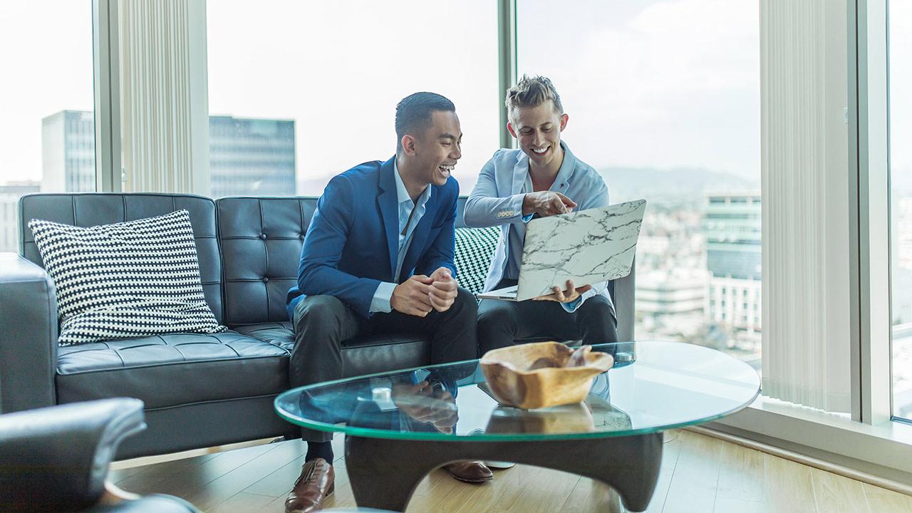 Zwei Arbeitskollegen schauen auf einen Laptop.