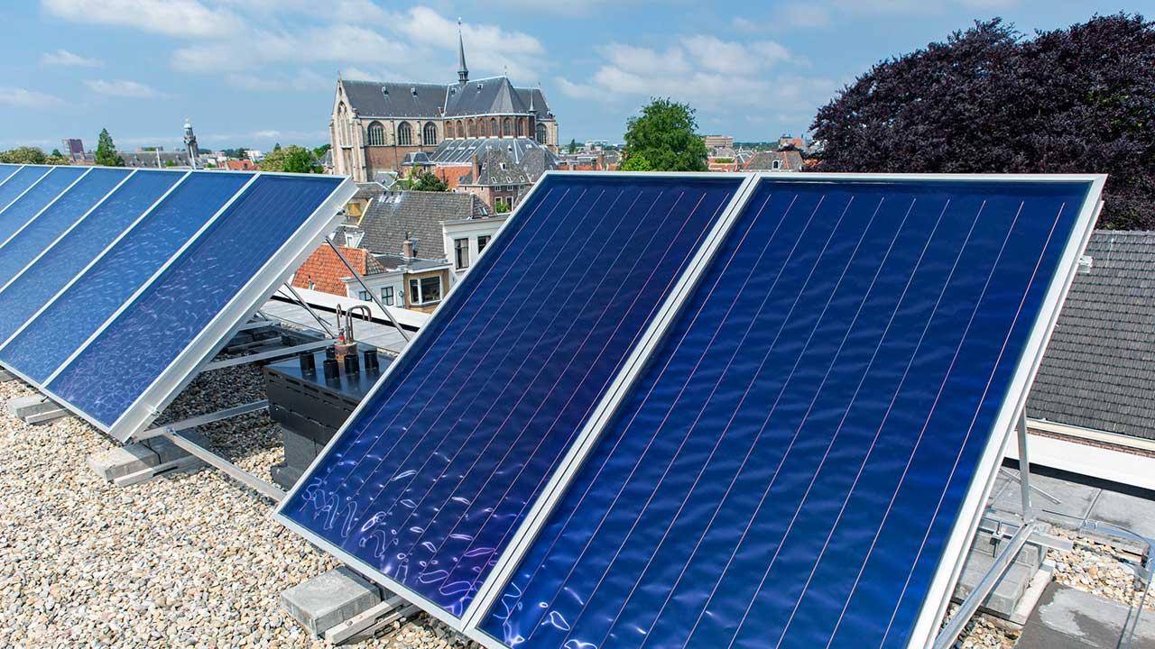 Sonnenkollektoren mit Kirchengebäude im Hintergrund in Leiden, Niederlande | (c) 123rf