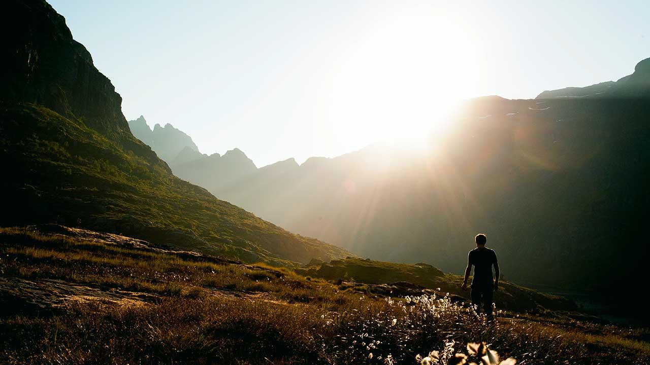 Mann auf den Lofoten, Norwegen wandert auf einer Wiese und blickt auf die Sonne, welche sich über einem Berggrat zeigt
