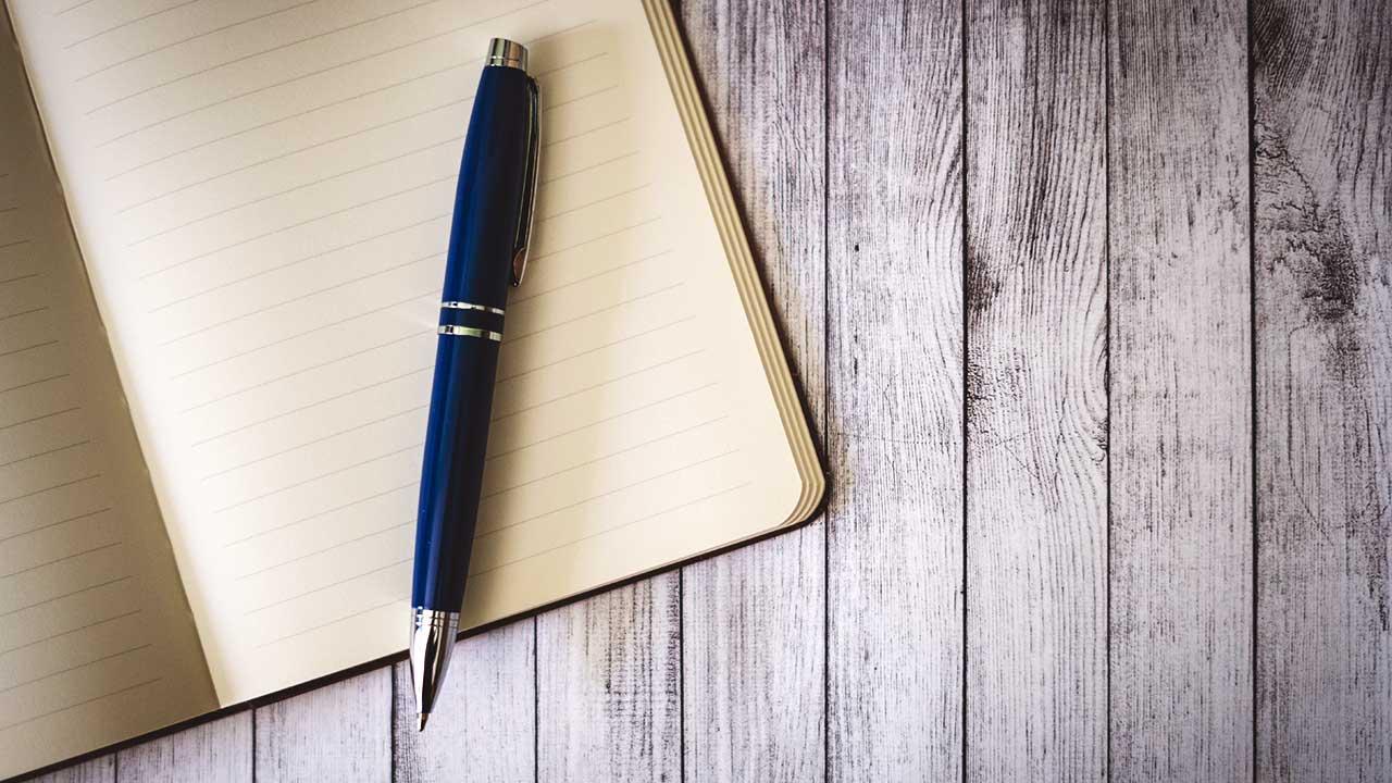 Offenes Schreibheft und Kugelschreiber liegen auf einem Holztisch