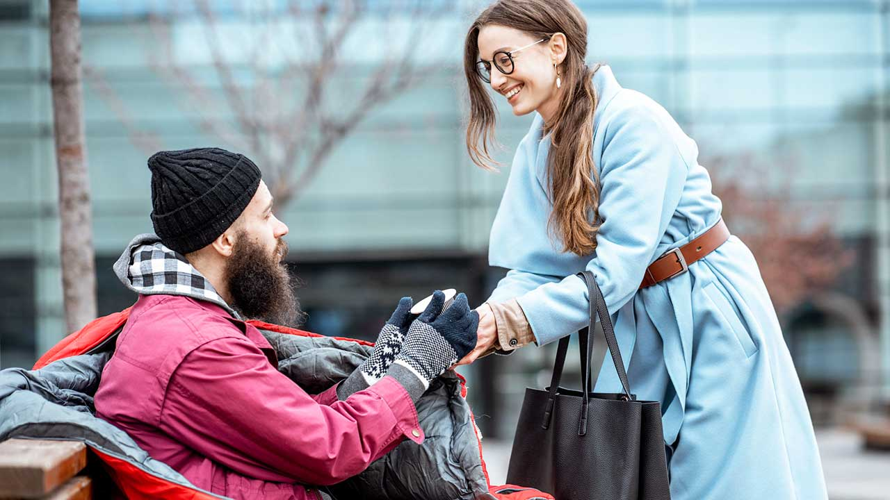 Eine Frau schenkt einem Obachlosen einen Becher