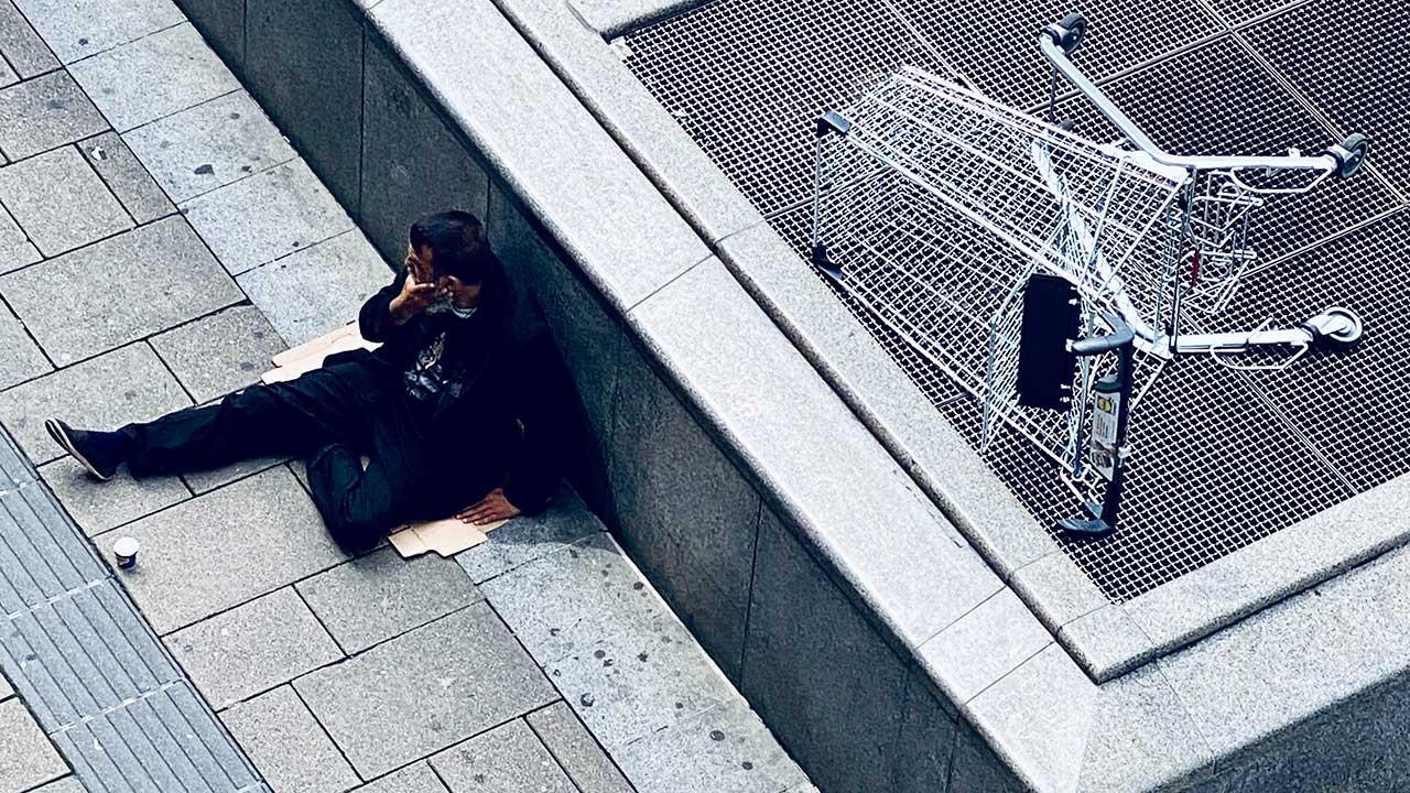 Bettelnder Mann in Wien sitzt vor Rolltreppe