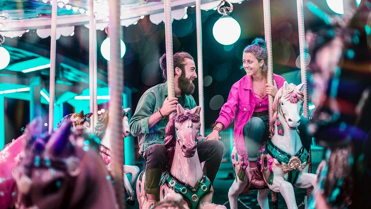 Erwachsenes Paar reitet auf einen Karussell und hat Spass daran
