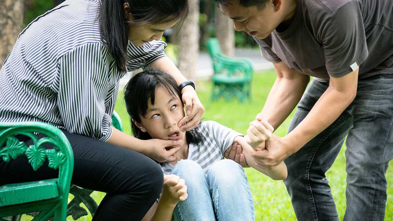 Eltern helfen ihrer Tochter bei einem epileptischen Anfall