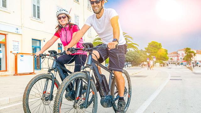 Paar geniesst seine Fahrt auf den E-Bikes