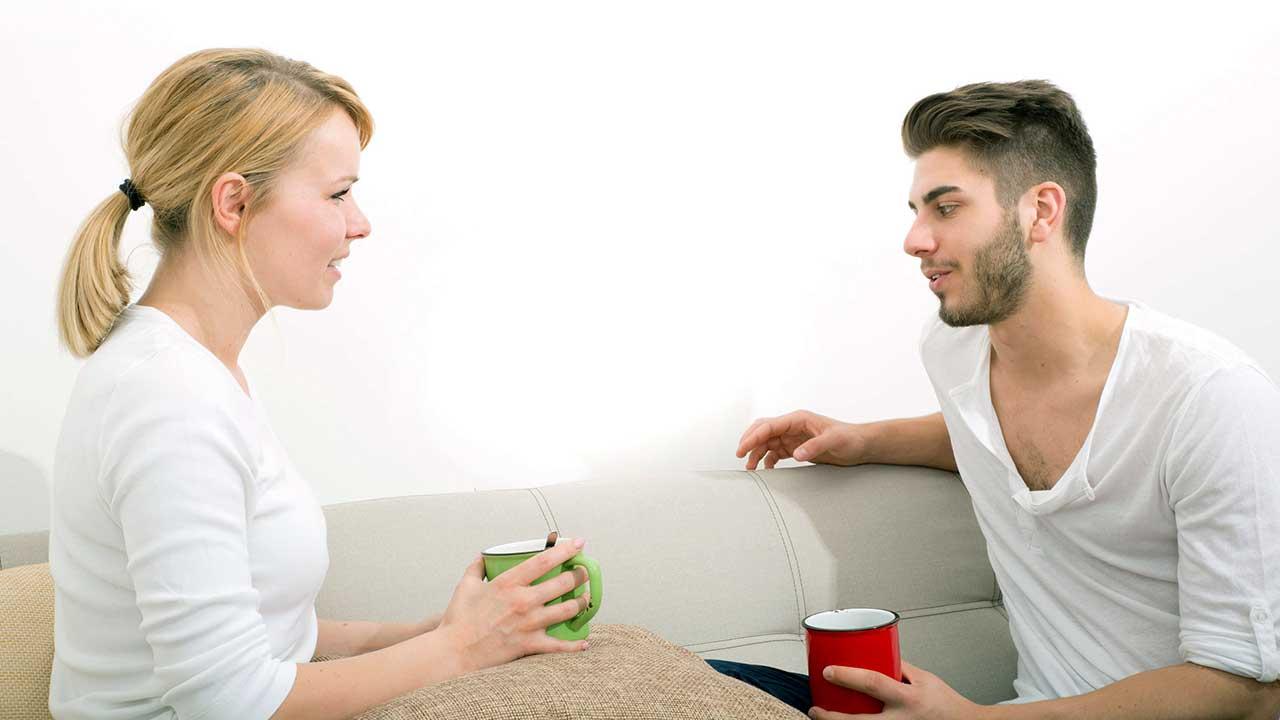 Ein junges Paar sitzt auf dem Sofa, mit Tassen in den Händen und führt ein Gespräch