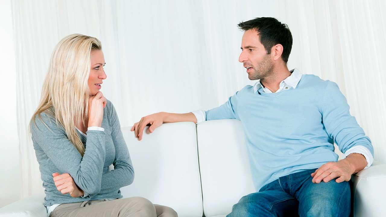 Frau und Mann sitzen auf einem Sofa und führen ein anspruchsvolles Gespräch