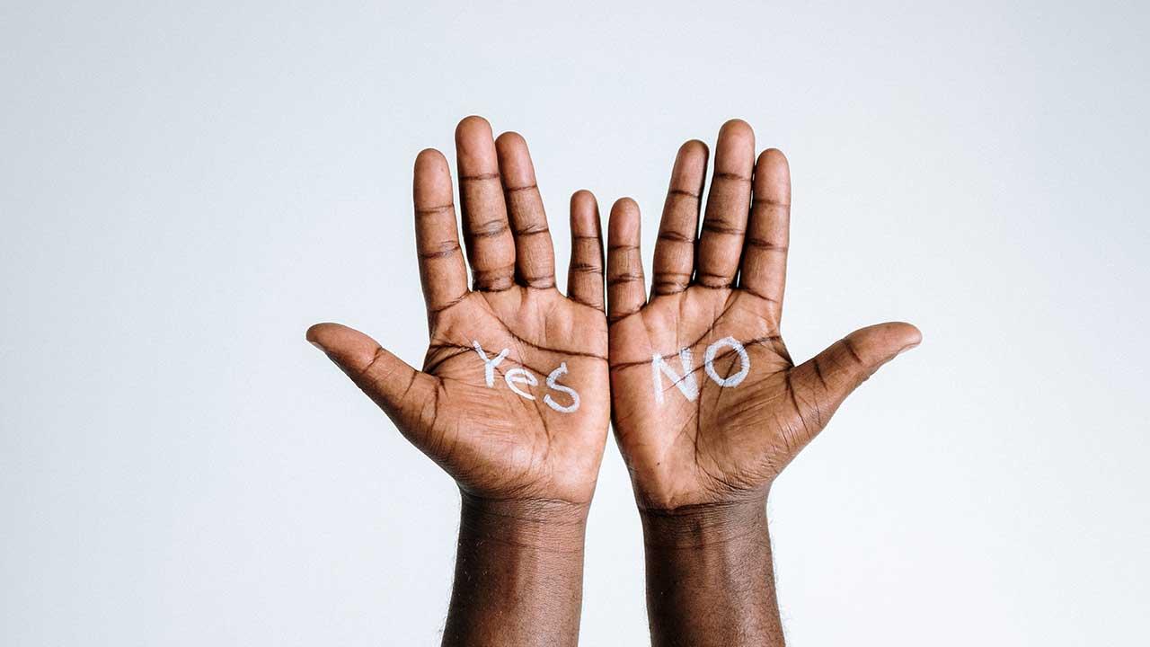 Zwei Hände, wo jeweils Yes und No geschrieben steht