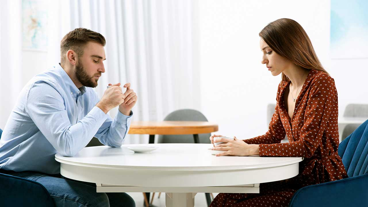 Paar sitzt schweigend an einem Tisch