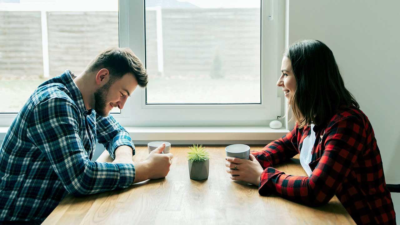 Ein Paar sitzt an einem Tisch und freut sich schmunzelnd und lächelnd aneinander