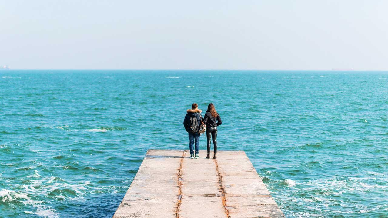Rückansicht auf ein junges Paar, welches am Rand eines Piers mit Blick auf das Meer steht