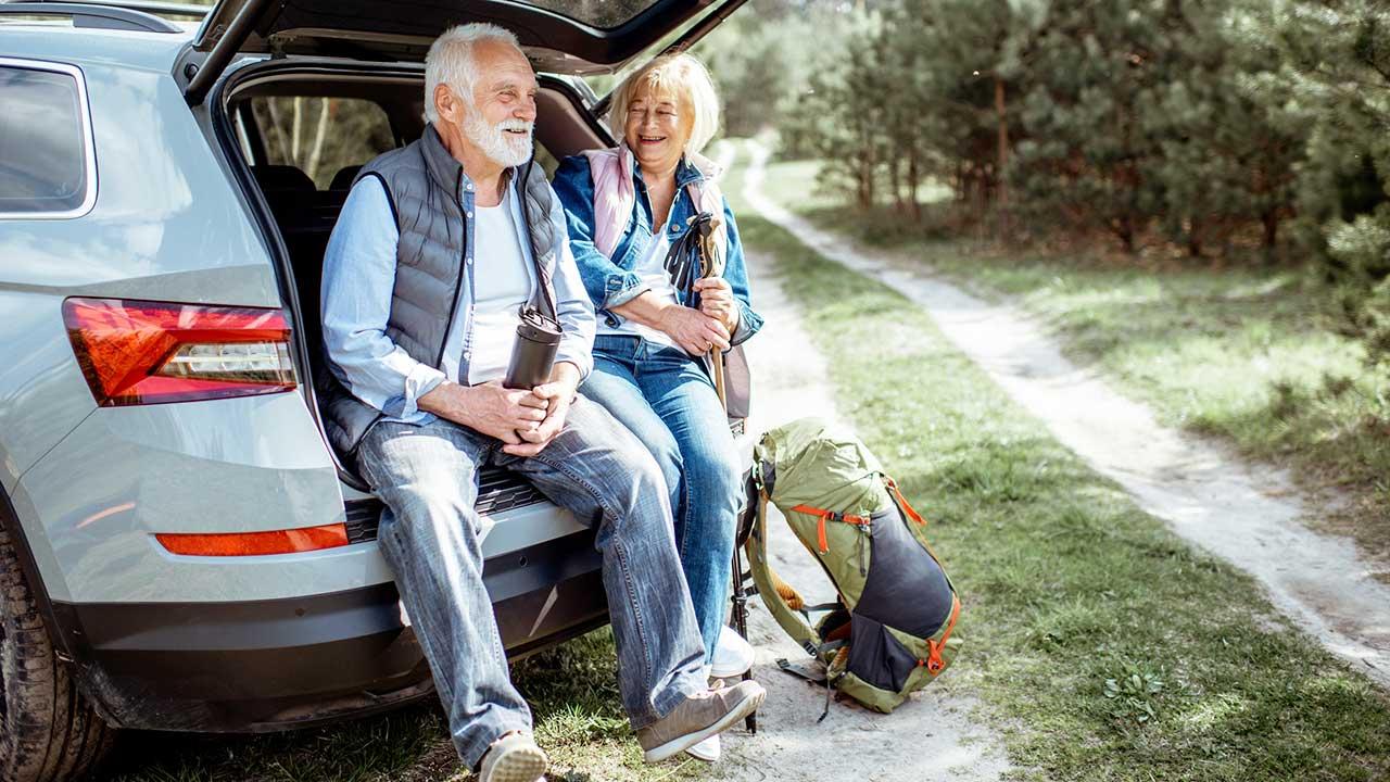 Seniorenpaar auf Reise sitzt im offenen Kofferram und macht Pause