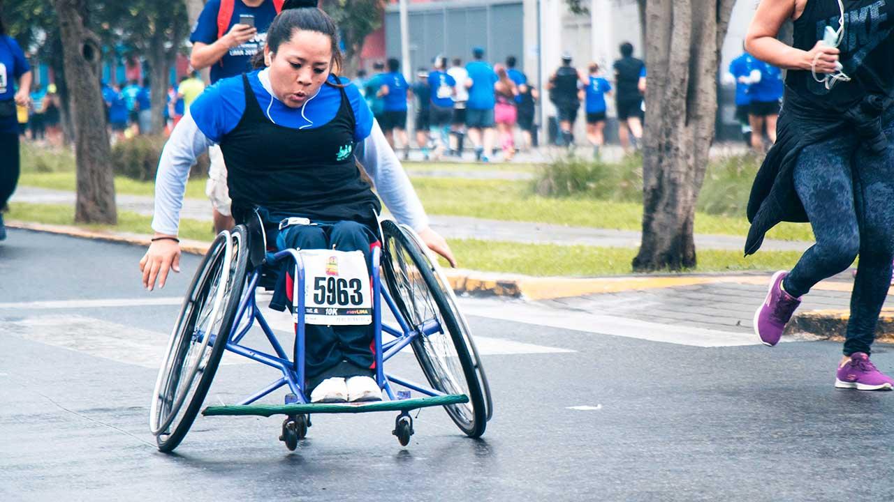 Frau in einem Rollstuhl nimmt an einem Marathon teil