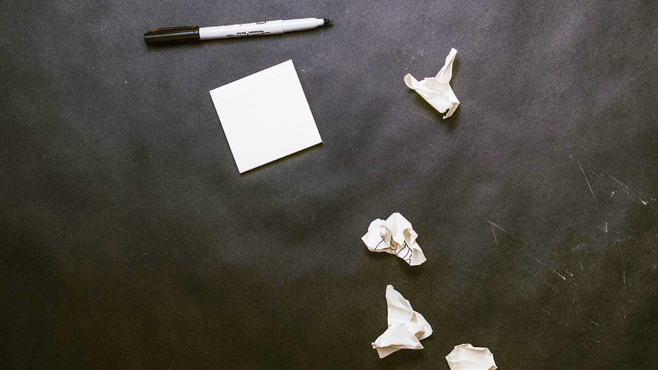 Post-its und Stift auf einer dunklen Oberfläche
