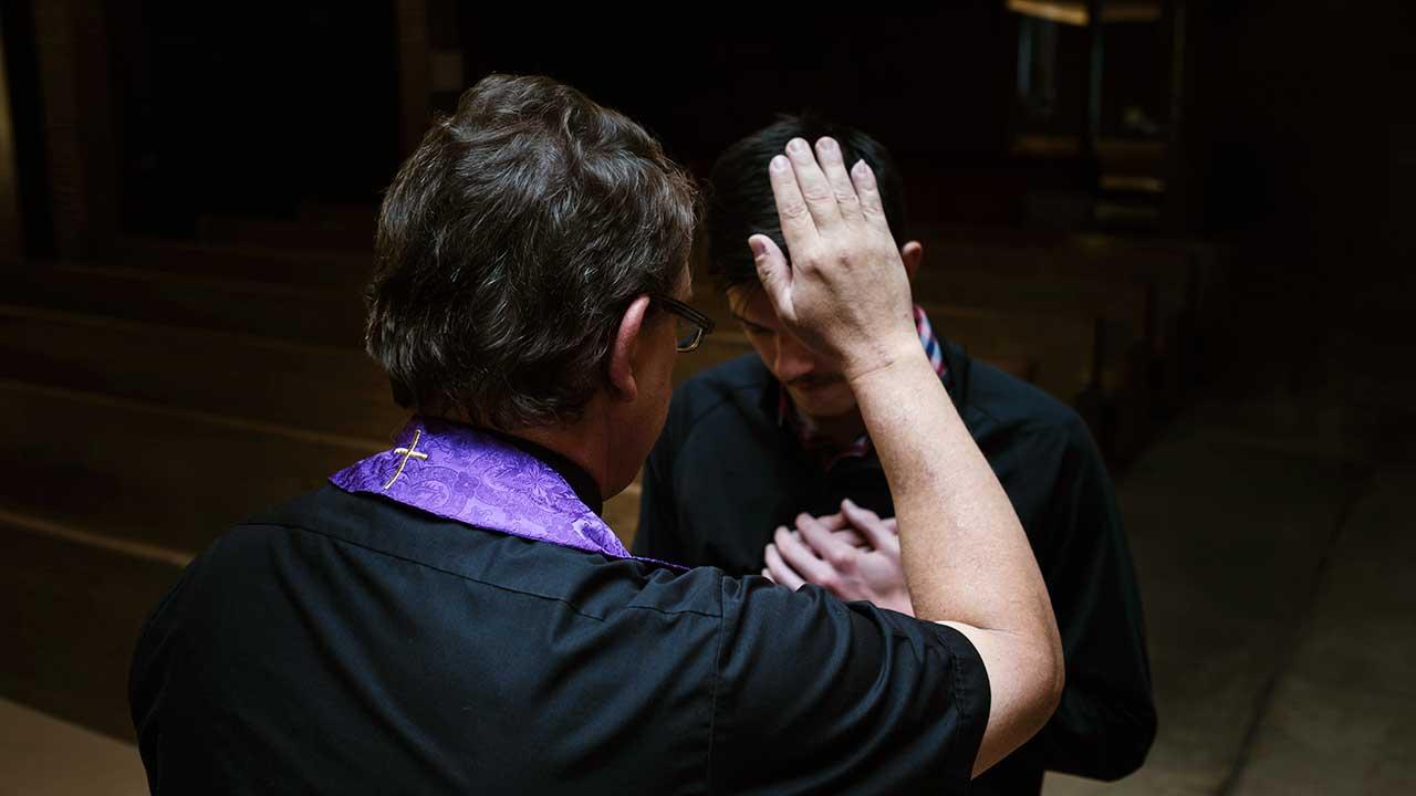 Priester segnet einen Mann, indem er eine Hand über den Kopf des anderen hält