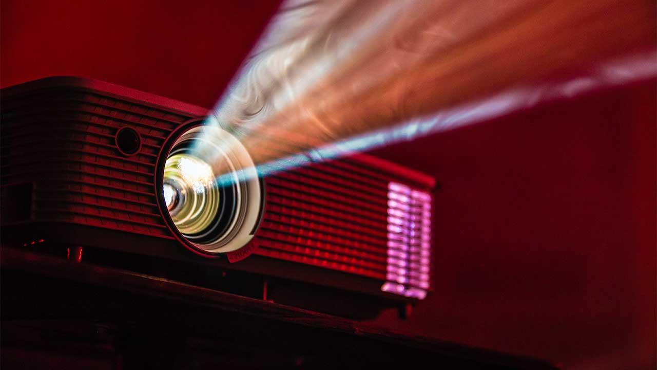 Projektor in der Dunkelheit mit Lichtstrahlen