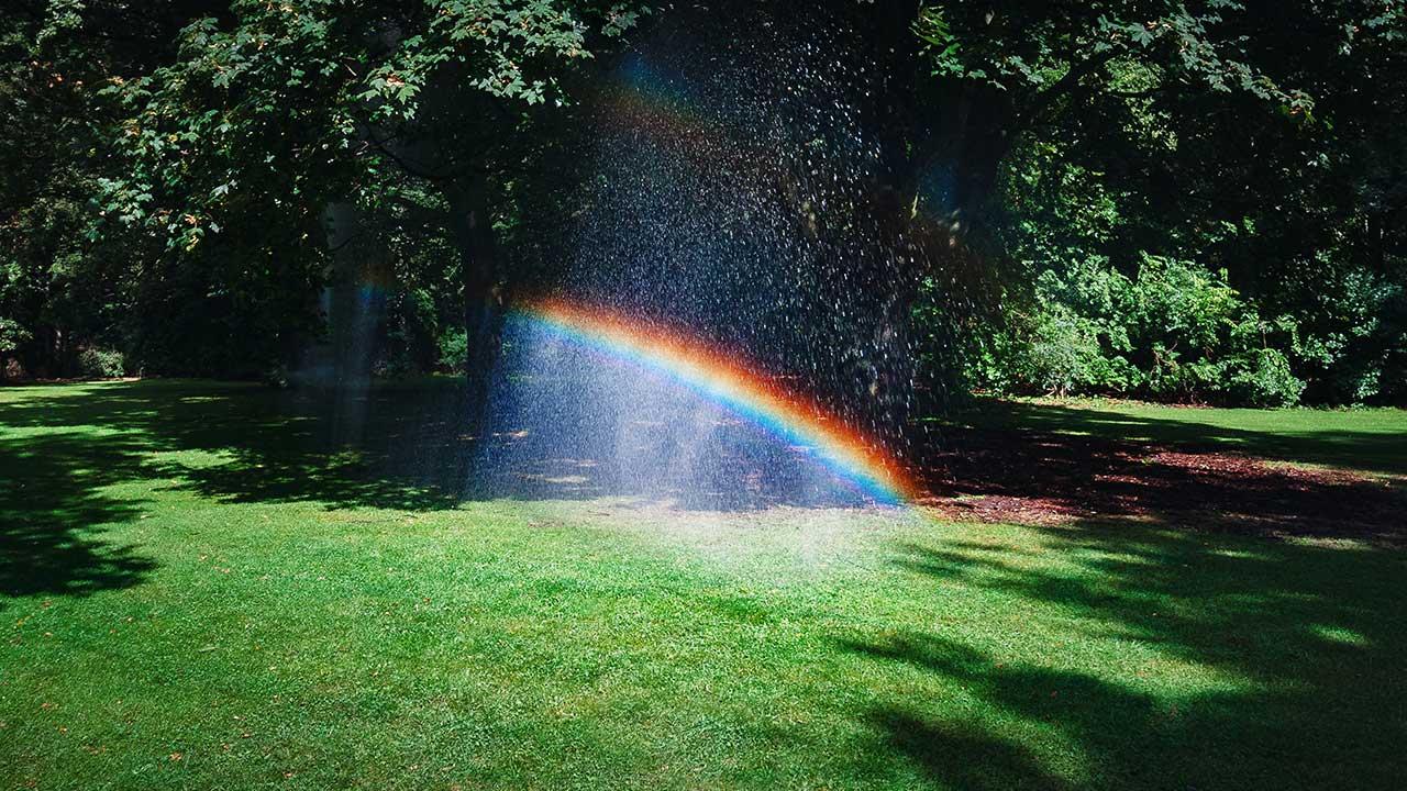 Licht scheint durch einen Wasserstrahl und so entsteht ein Regenbogen.