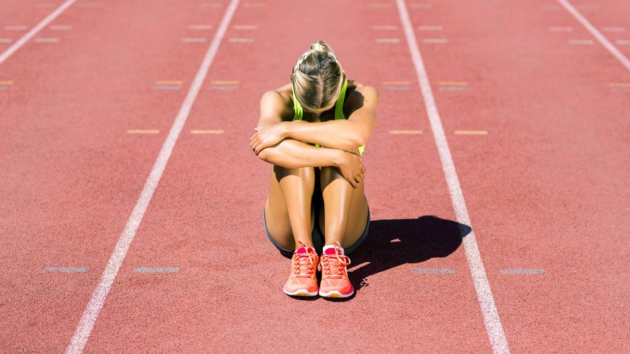 Erschöpfte Sportlerin sitzt auf der Rennbahn