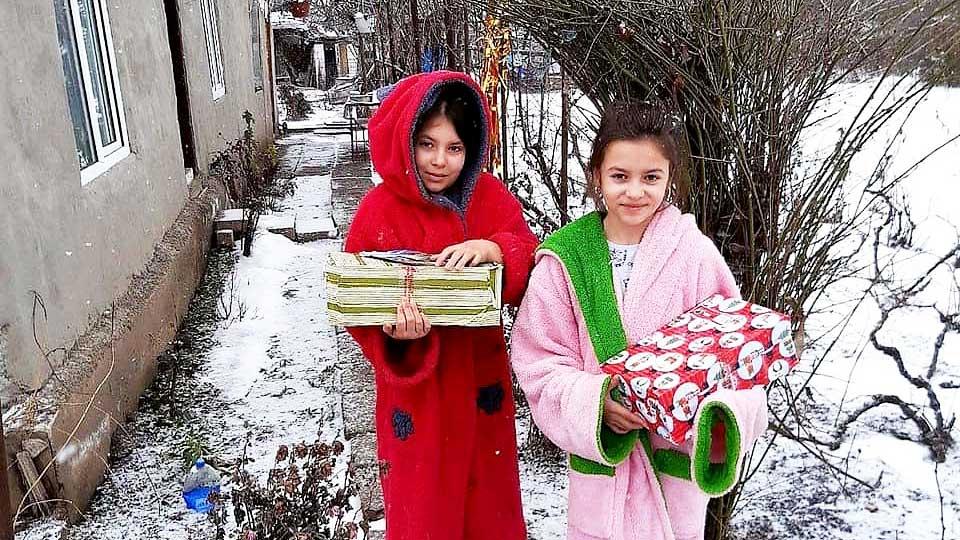 Weihnachten im Schuhkarton: zwei Mädchen in Rumänien freuen sich über ihre Geschenke
