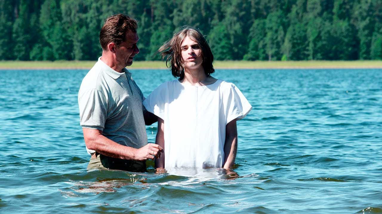 Älterer tauft jüngeren Mann in einem Gewässer in Russland