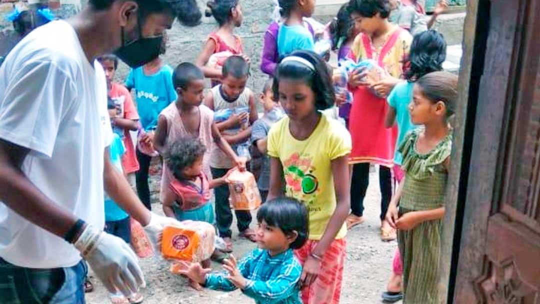 Ein Mitarbeiter von SAM global verteilt Nahrungsmittel an Kinder