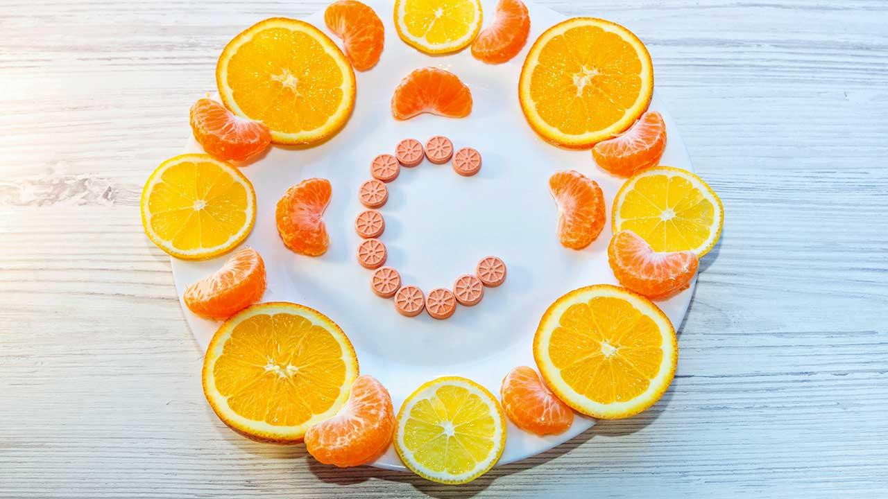Scheiben von Zitrusfrüchten und Vitamin-C-Pillen