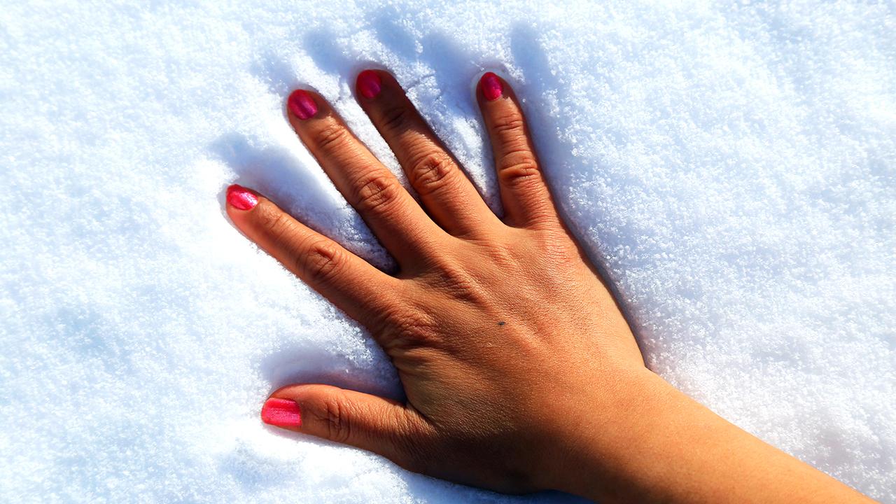 Hand im kalten Schnee