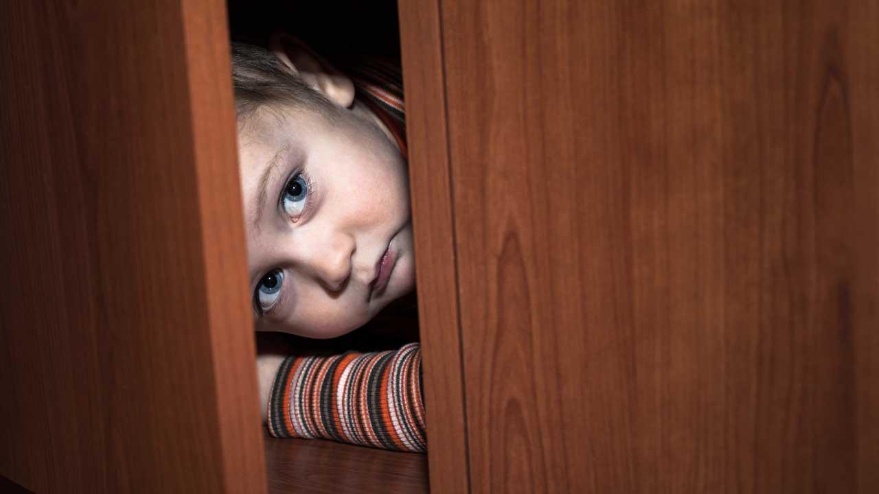 Kind hat sich im Schrank versteckt und blickt aus der offenen Tür hervor