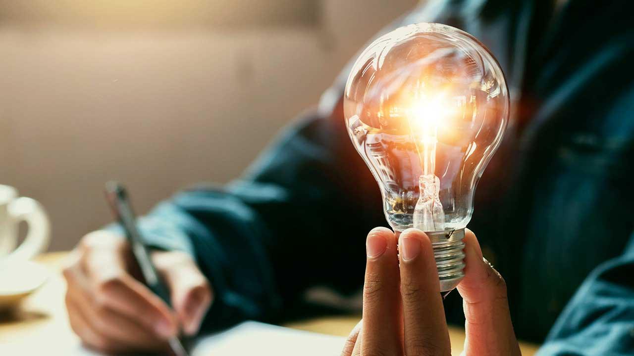Männerhände halten Glühbirne und Schreiber