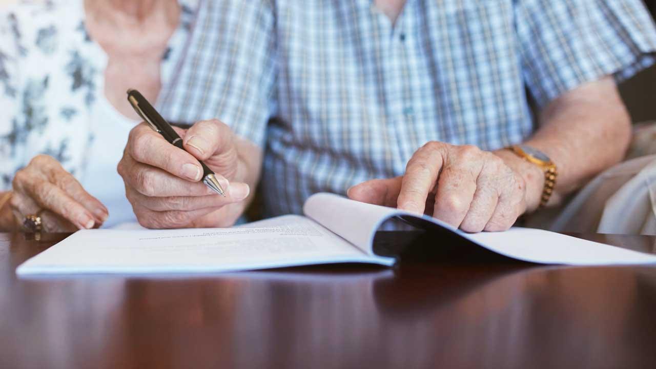 Seniorenpaar unterschreibt ein Dokument