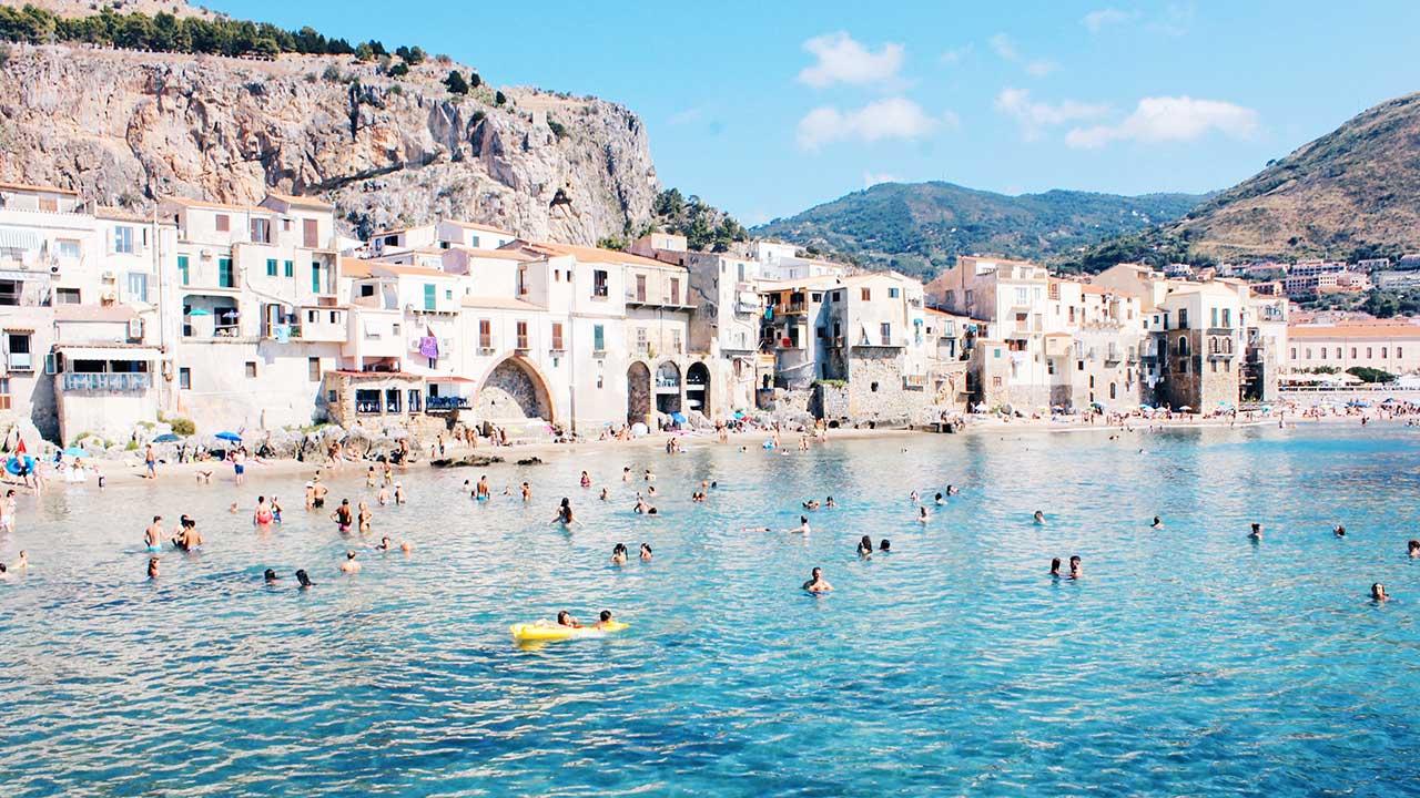 Badende am Strand von Cefalù in Sizilien