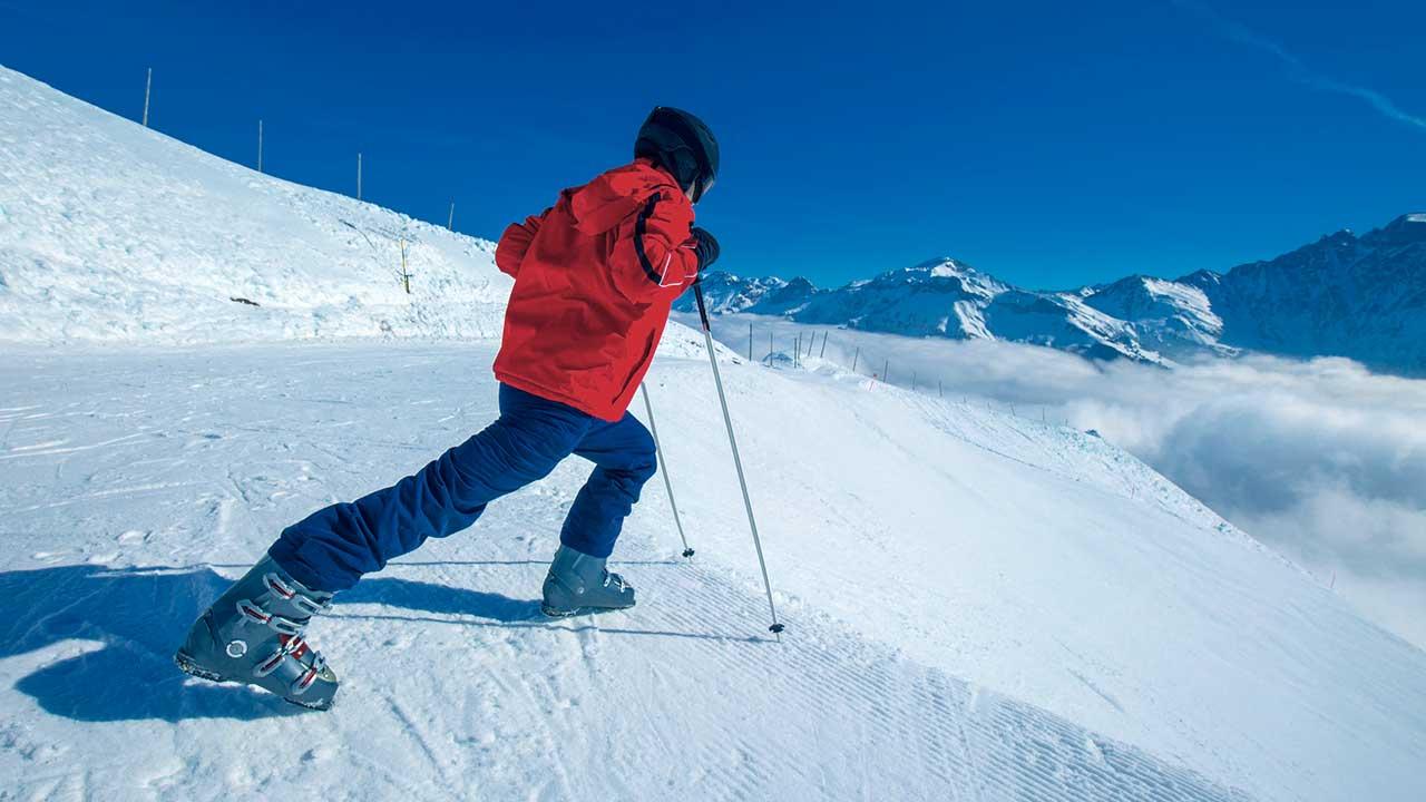 Skifahrer macht Dehnübung auf der Piste