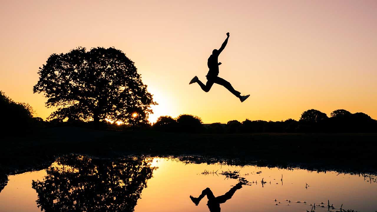 Silhouette eines Mannes springt bei Sonnenaufgang oder -untergang über eine Wasserfläche