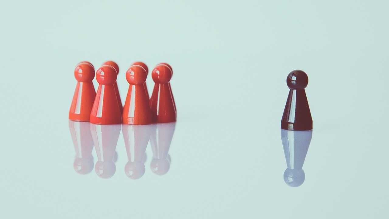 Gruppe von roten Spielfiguten und eine einzelne schwarze Spielfigur