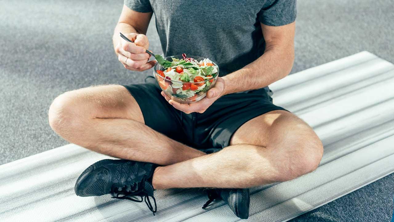 Sitzender Sportler isst Salat