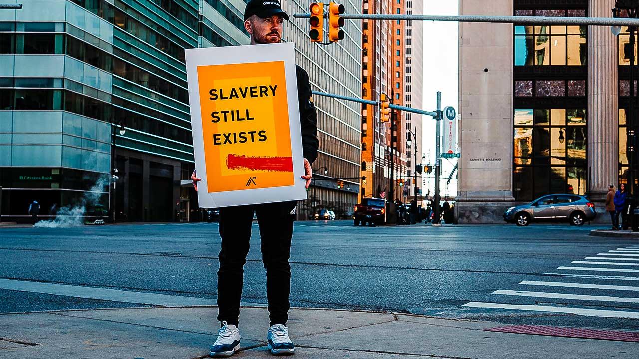 Mann hält Plakat «Slavery still exists», Sklaverei existiert immer noch