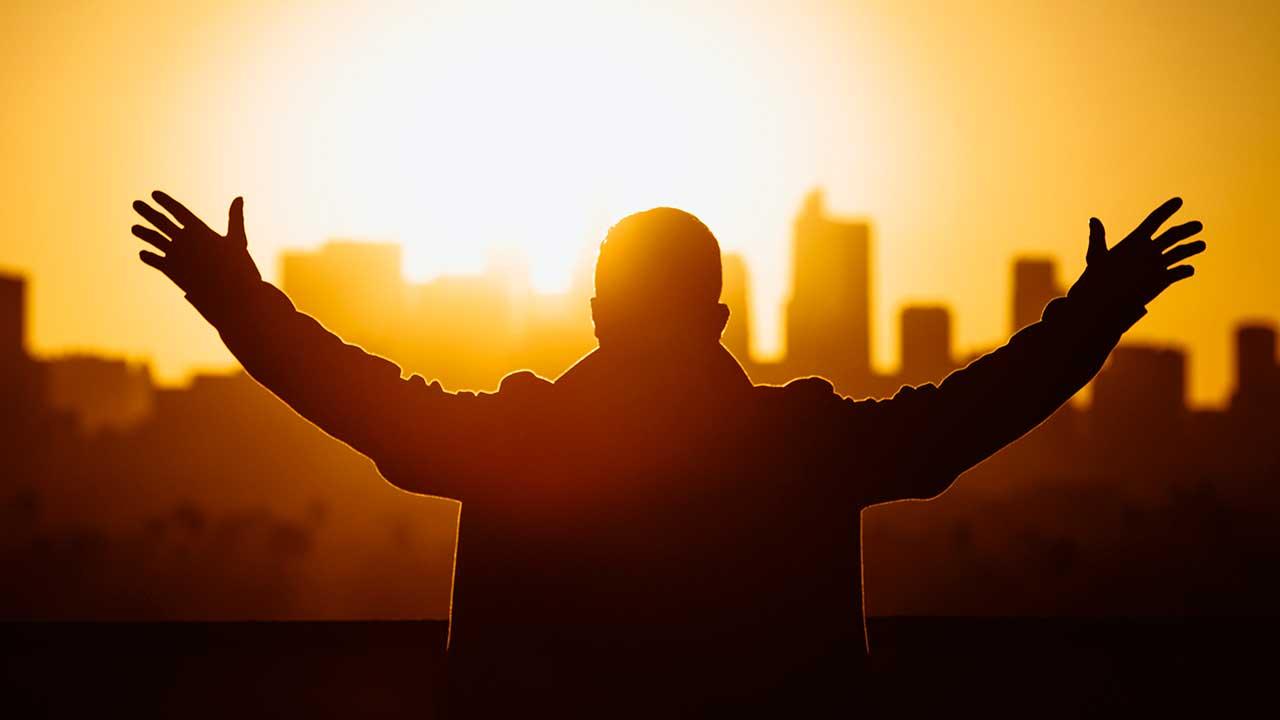 Mann streckt vor einem orange-gelb gefärbten Himmel seine Arme aus