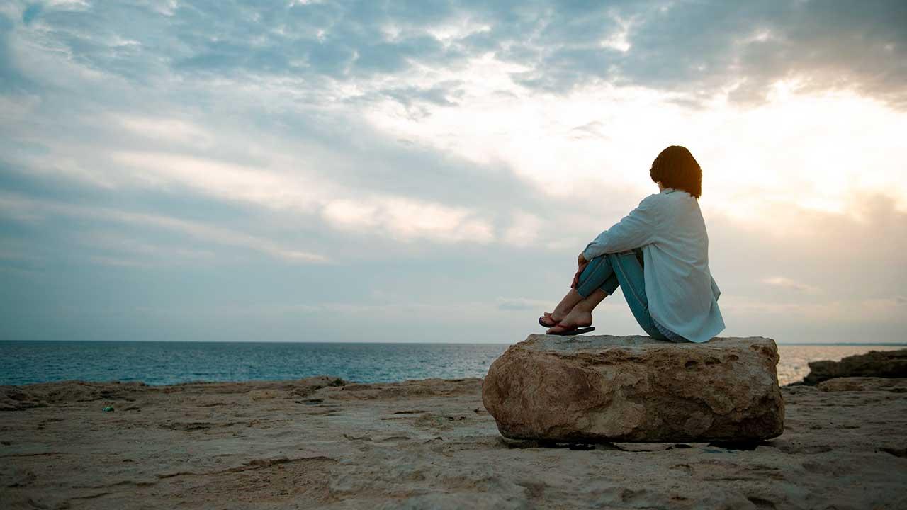 Frau sitzt am Strand auf einem grossen Stein und blickt zum Himmel hoch, wo Sonnenlicht am bewölkten Himmel zu sehen ist