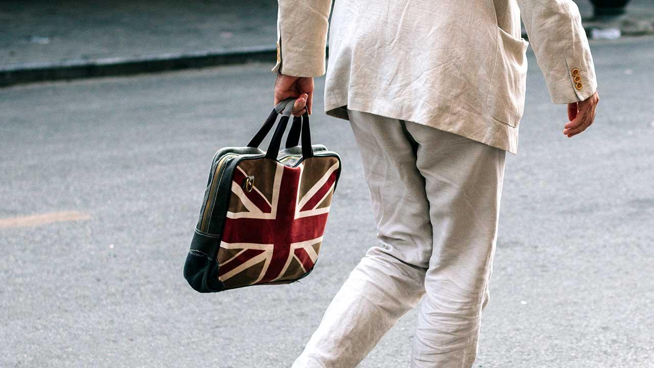 Mann mit Tasche im Union-Jack-Design läuft durch die Strasse