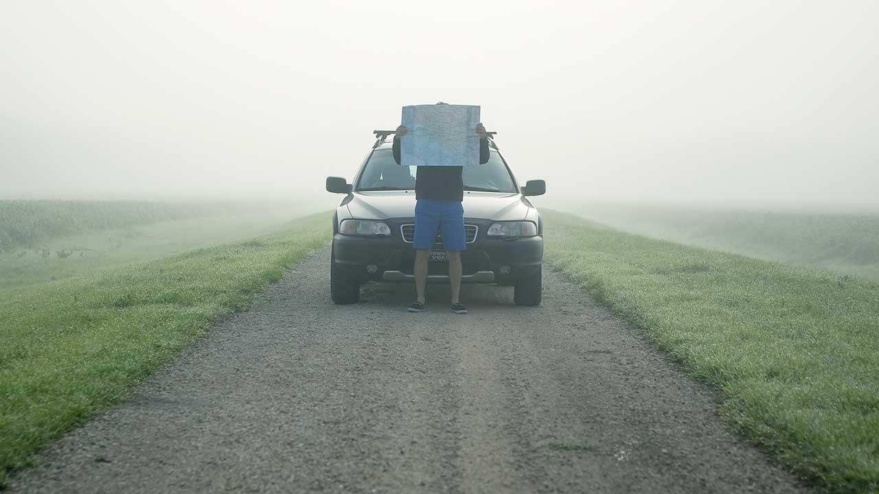 Mann mit Landkarte vor seinem Kopf steht vor seinem Auto