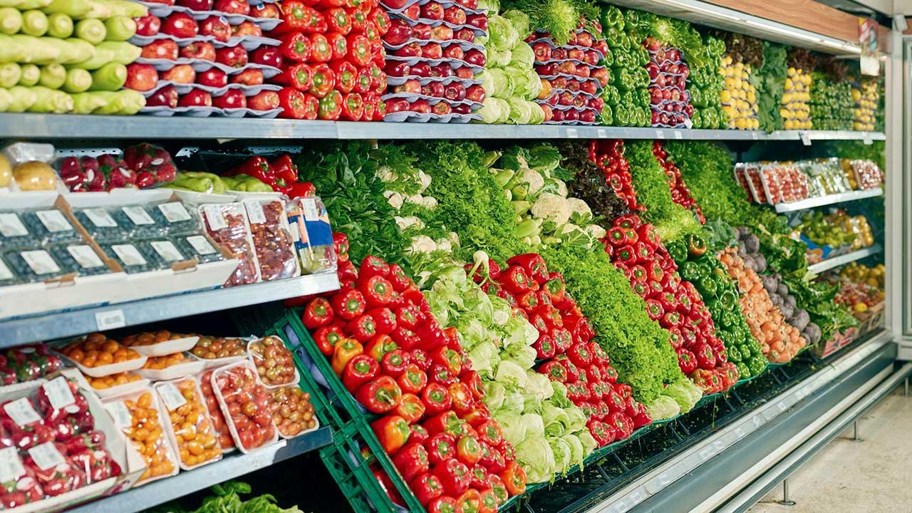 Gefüllte Regale mit Gemüse und Salat in einem Supermarkt