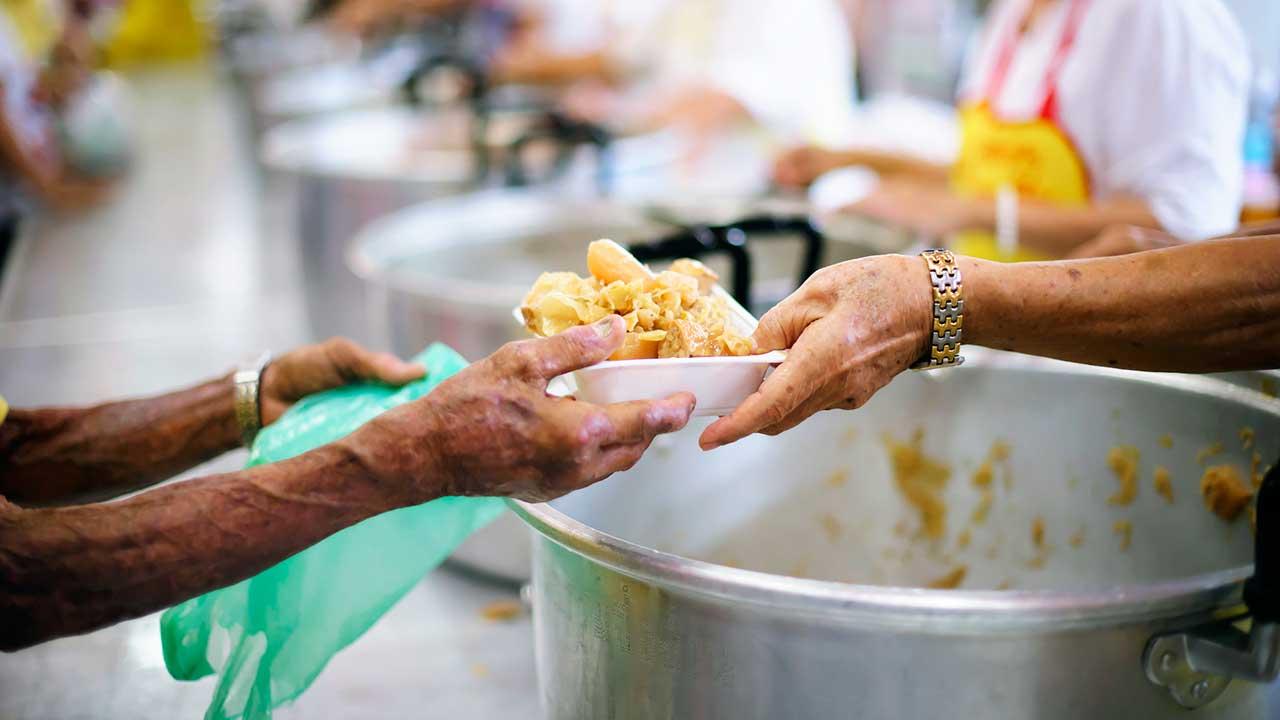 In einer Suppenküche übergeben die Hände eines Mitarbeiters eine Portion Essen an einen Bedürftigen