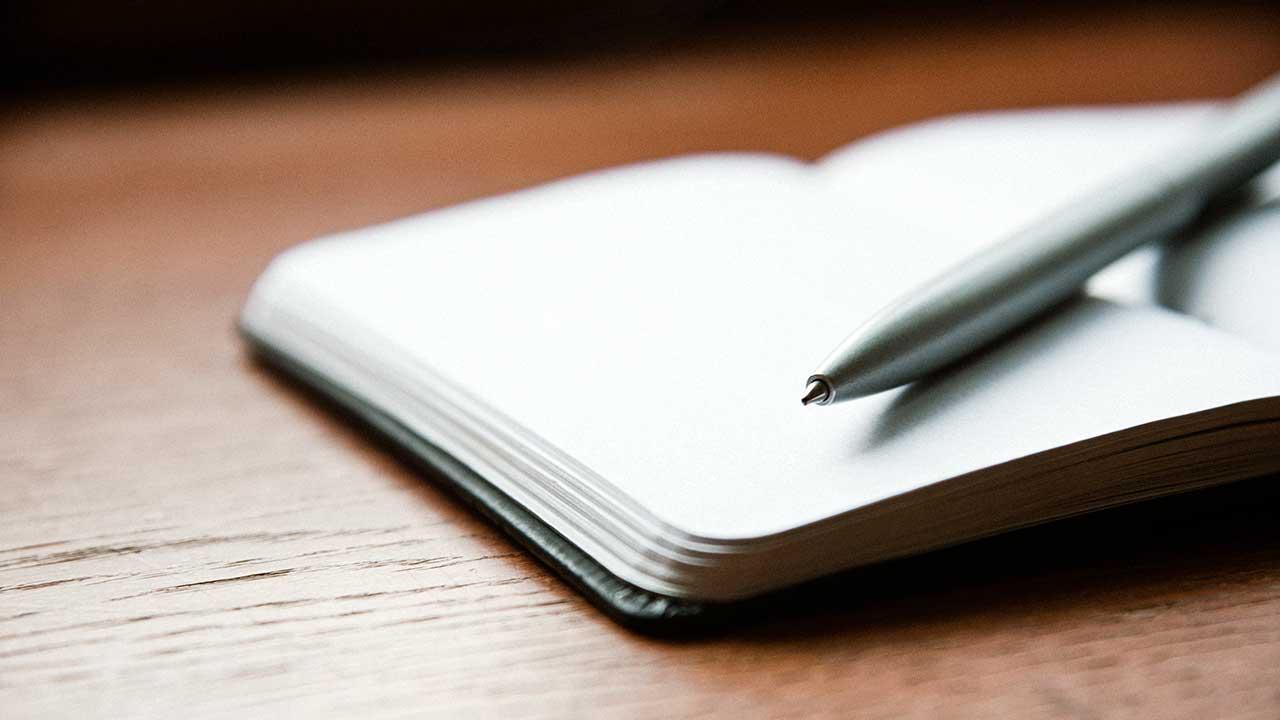Offenes Tagebuch mit Kugelschreiber auf Holztisch